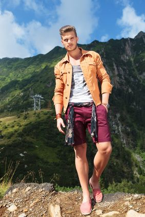 full length picture of a young casual man standing with a hand in his pocket, in the mountains, and looking into the camera