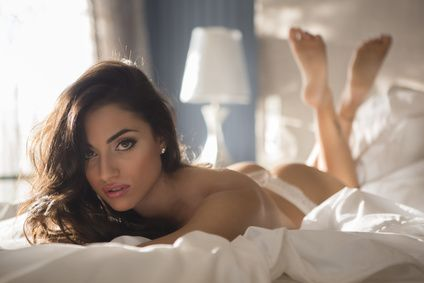 Sexy woman lying down on the bed