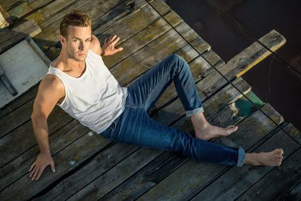 Cute barefoot guy lies on the wooden surface outdoors. He wears a white singlet and blue jeans and looks into the camera while leans on his hands. Photographed from the upper point. Horizontal.